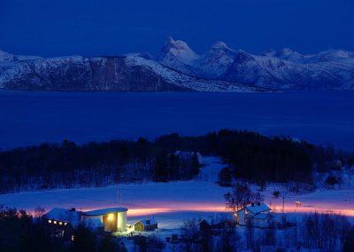 Stetind og Skarberget i Tysfjord i blåtimen med fjord og snøkledd fjell og gård i forgrunn